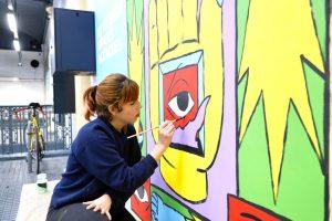 Noia pintant mural FGC