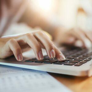 Noia escrivint a un ordinador portàtil