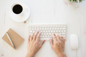 Persona escrivint al teclat de l'ordinador