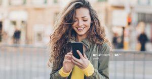Noia mirant el mòvil al carrer